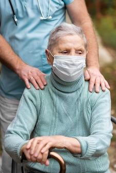 Oudere vrouw met medisch masker en verpleger bij verpleeghuis