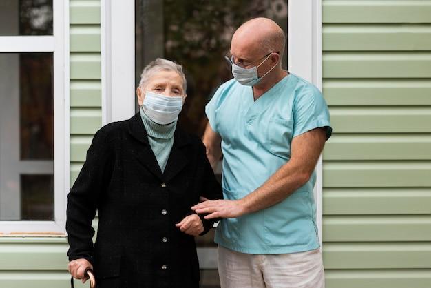 Oudere vrouw met medisch masker geholpen door haar verpleger