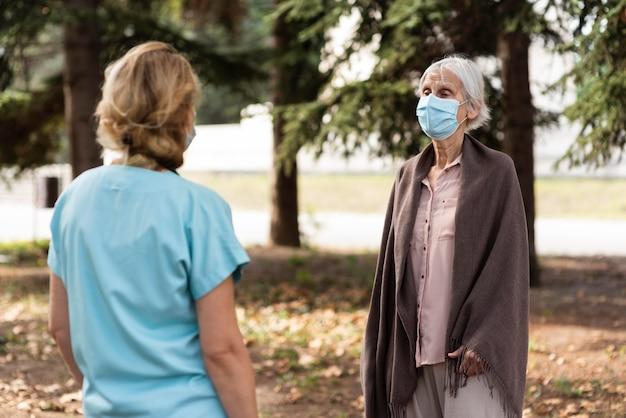 Oudere vrouw met medisch masker in gesprek met vrouwelijke verpleegster buitenshuis