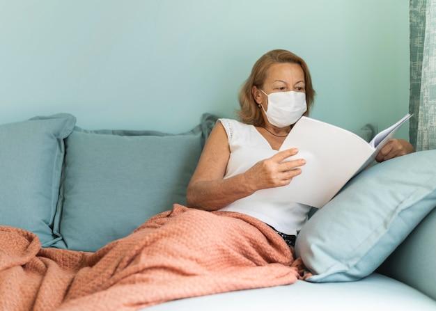 Oudere vrouw met medisch masker thuis tijdens de pandemie die een boek leest