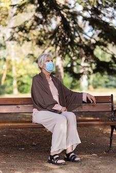 Oudere vrouw met medisch masker zittend op een bankje