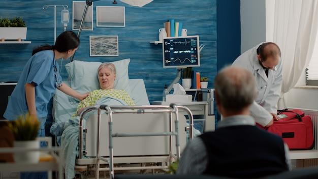Oudere vrouw met ziekte die bezoek krijgt van arts en verpleegster