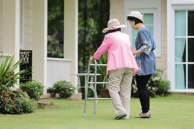 Oudere vrouw oefenen wandelen in de achtertuin met dochter
