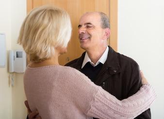 Oudere vrouw ontmoeting man in de buurt van de deur