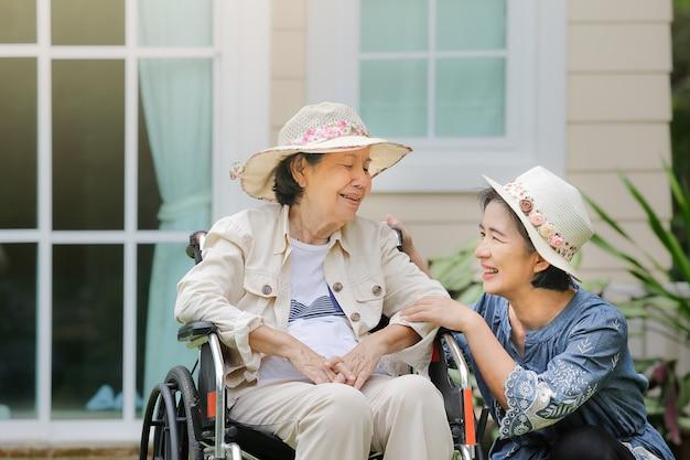 Oudere vrouw ontspannen op rolstoel in achtertuin met dochter