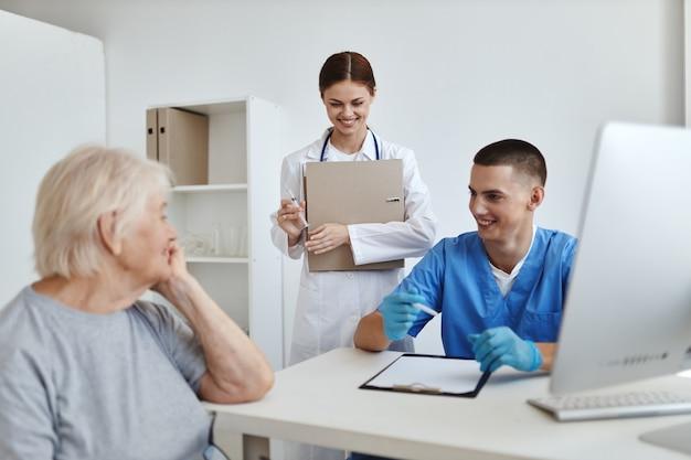 Oudere vrouw patiënt bij doktersafspraak en verpleegkundig ziekenhuisonderzoek