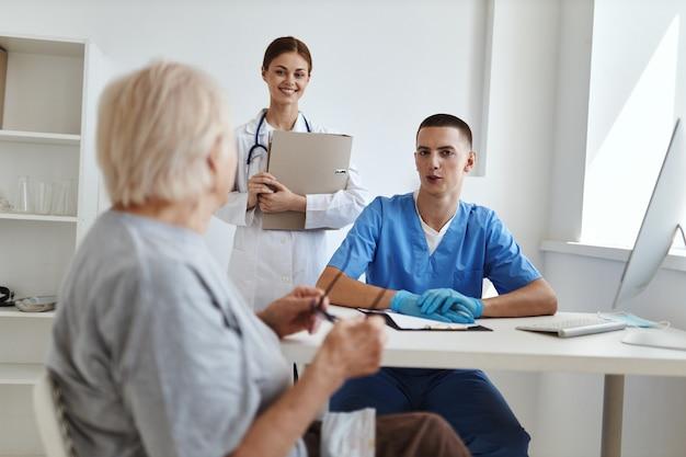 Oudere vrouw patiënt bij doktersafspraak en verpleegkundige op kantoor