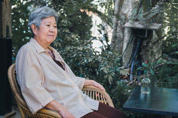 Oudere vrouw rusten in de tuin. aziatische oudere vrouw buiten ontspannen. senior vrije levensstijl