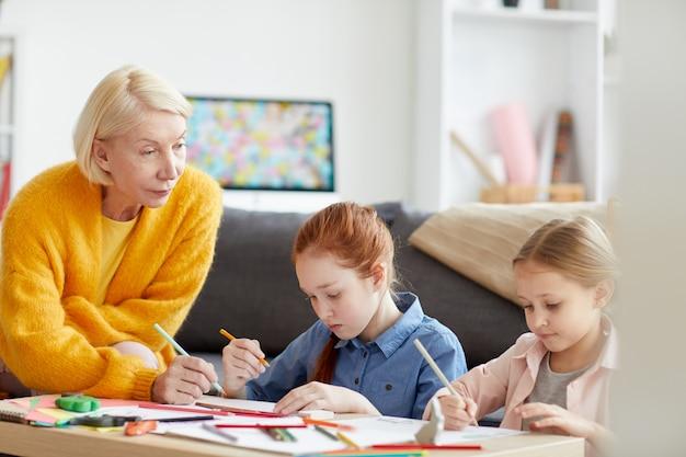 Oudere vrouw tekenen met twee kinderen
