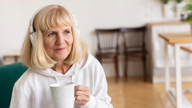 Oudere vrouw thuis genieten van koffie en muziek op de koptelefoon