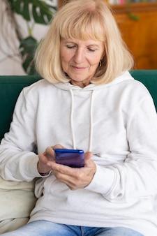 Oudere vrouw thuis met behulp van smartphone op de bank