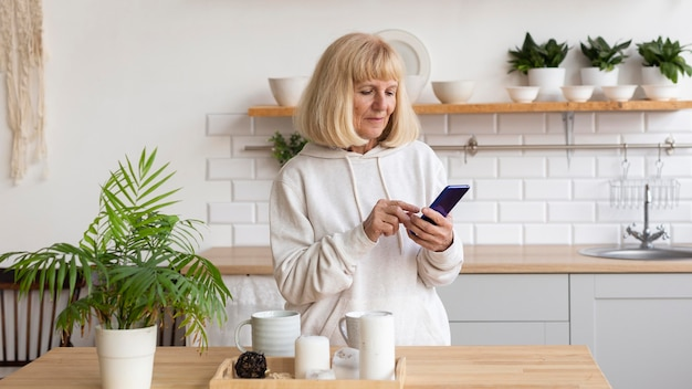 Oudere vrouw thuis met behulp van smartphone