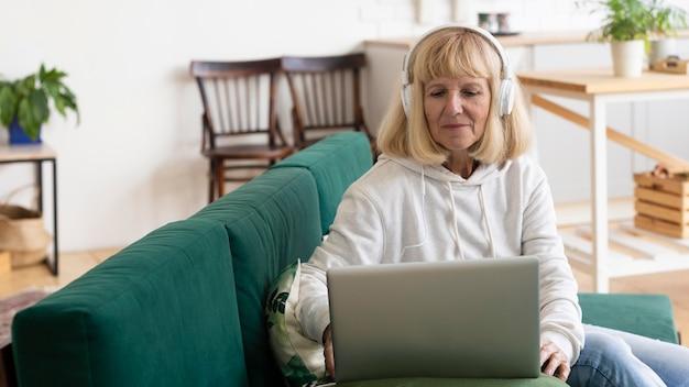 Oudere vrouw thuis met hoofdtelefoons en laptop