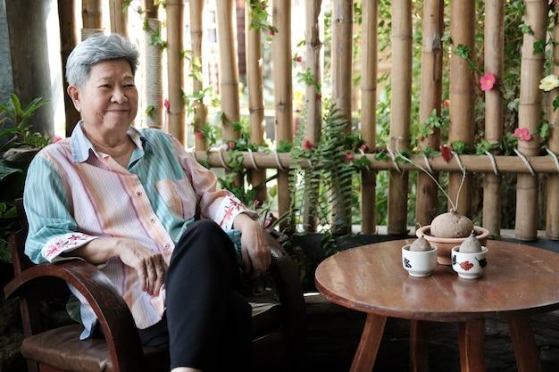 Oudere vrouw thuis rusten. aziatische bejaarde vrouw zittend op een stoel. senior vrije levensstijl