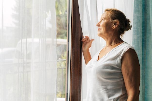 Oudere vrouw thuis tijdens de pandemie die door het raam kijkt