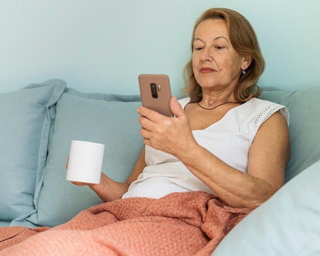 Oudere vrouw thuis tijdens de pandemie genieten van een kopje koffie en het gebruik van smartphone