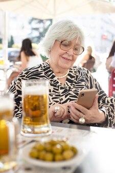 Oudere vrouw typt op haar mobiele telefoon terwijl ze op een terras een biertje drinkt