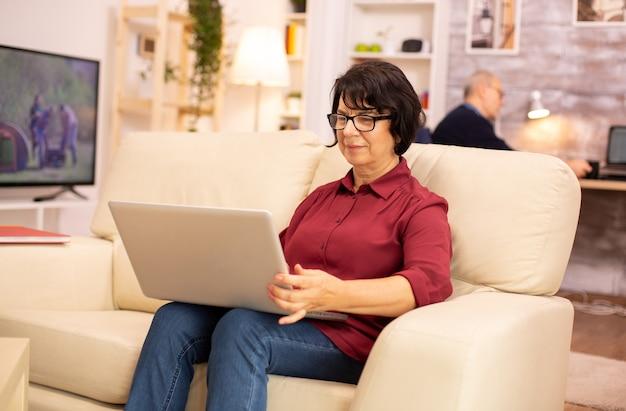 Oudere vrouw van in de zestig die op de bank zit met een laptop, oude mensen die nieuwe technologie gebruiken