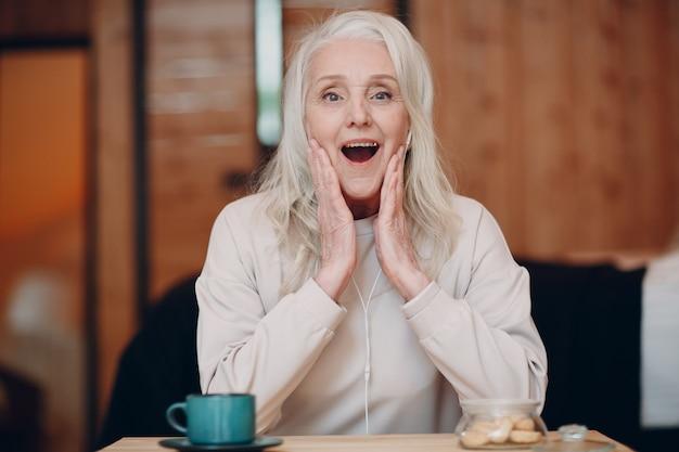 Oudere vrouw verbaasd met koptelefoon pratend videogesprek op laptop in keuken zwaaiend naar scherm chatten