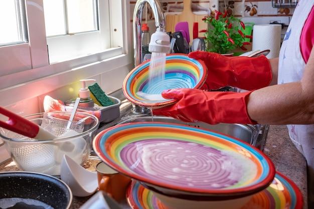 Oudere vrouw wast servies voor het raam, met rode handschoenen aan. thuiskeuken en kleurrijke gerechten onder stromend water