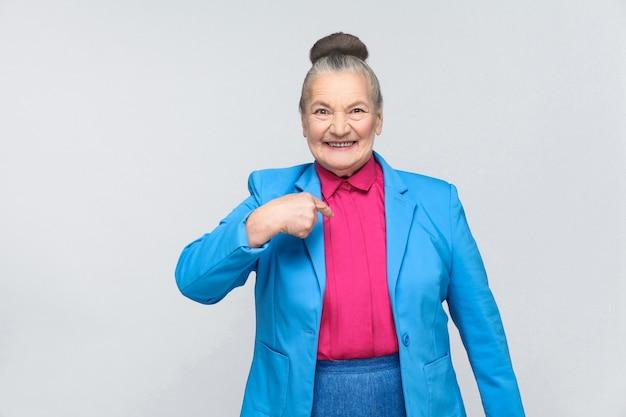 Oudere vrouw wijst zelf met de vinger en glimlacht met tanden