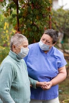 Oudere vrouw wordt verzorgd door vrouwelijke verpleegster