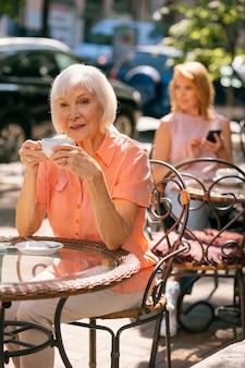 Oudere vrouw zit aan de cafétafel in de straat op een zonnige dag met een kopje koffie