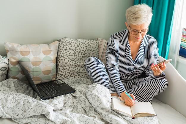 Oudere vrouw zit op het bed in pyjama