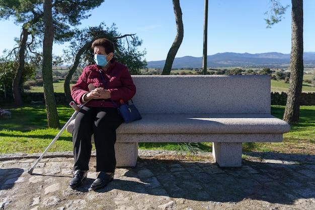 Oudere vrouw zittend op een bankje met sociale afstand nemen vanwege coronavirus.