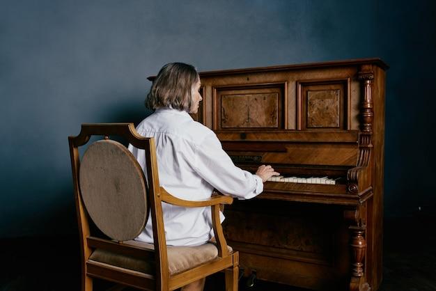 Oudere vrouw zittend op een stoel in de buurt van de uitvoering van de pianomuziek