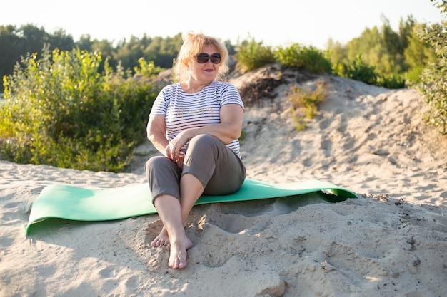 Oudere vrouw zittend op een zand in zomer-strand