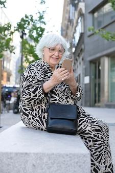Oudere vrouw zittend op straatbank met mobiele telefoon