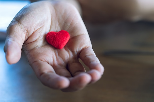 Oudere vrouwelijke handen die weinig rood hart geven.