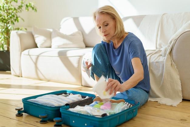 Oudere vrouwelijke verpakking met gasmasker tijdens het inpakken van de koffer voor een reisreis tijdens covod