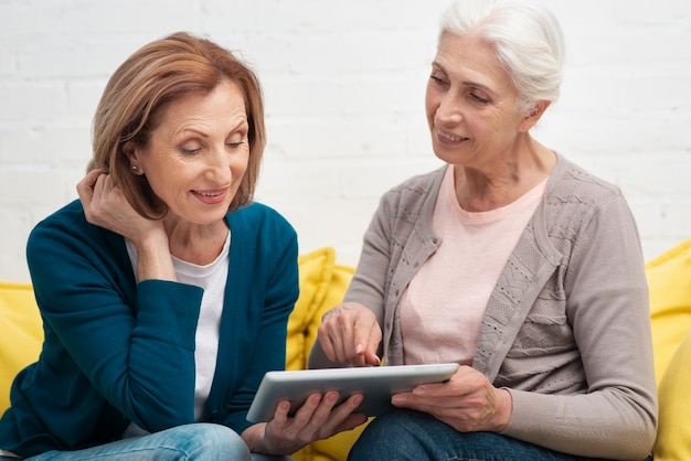 Oudere vrouwen die een tablet doorbladeren
