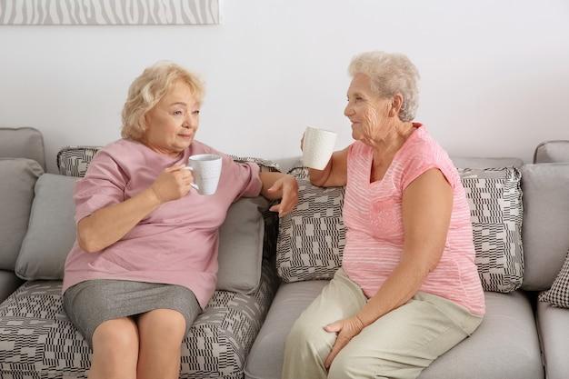 Oudere vrouwen die koffie drinken terwijl ze thuis op de bank zitten