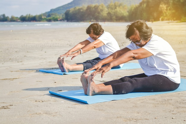 Oudere vrouwen oefenen op het strand aan zee frisse lucht, sterk lichaam
