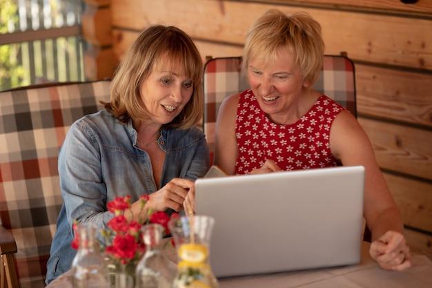 Oudere vrouwen van lange tijd lachen samen terwijl ze thuis naar de lap top kijken.