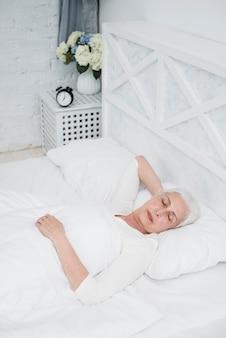 Oudere vrouwenslaap op een wit bed