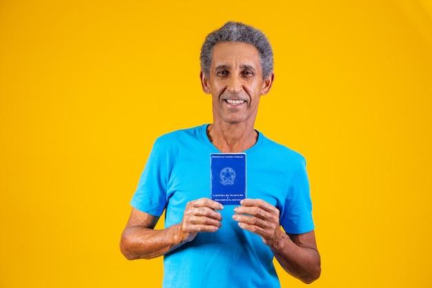 Oudere werknemer die een braziliaanse werkkaart in de hand houdt. oudere persoon met braziliaanse werkkaart