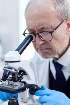 Oudere wetenschapper in moderne faciliteit die door een microscoop kijkt tijdens gezondheidszorgstudie. chemicus-onderzoeker in steriel laboratorium die experimenten doet voor de medische industrie met behulp van moderne technologie.
