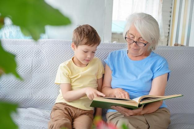 Oudere witharige vrouw met bril zit op de bank met jongen, met een open boek