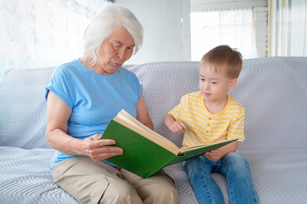 Oudere witharige vrouw zit op de bank met een kleine jongen en houdt een open boek op haar schoot