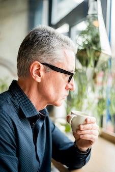 Oudere zakenman die van koffie heeft