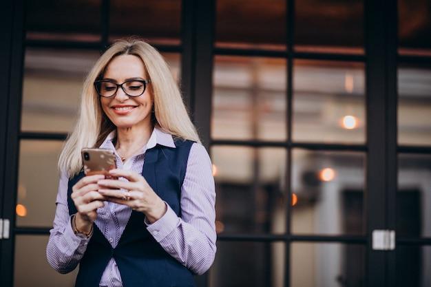 Oudere zakenvrouw buiten het café met behulp van de telefoon