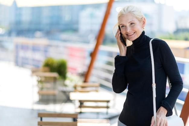 Oudere zakenvrouw buitenshuis op een telefoontje