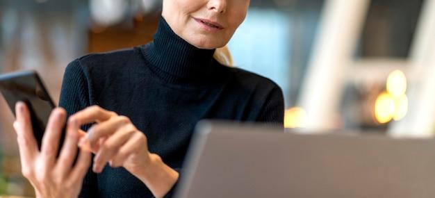 Oudere zakenvrouw die op laptop en smartphone werkt