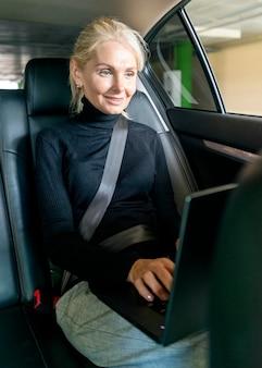 Oudere zakenvrouw die op laptop in de auto werkt