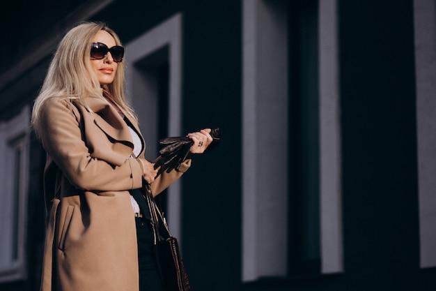 Oudere zakenvrouw in een jas buiten de straat