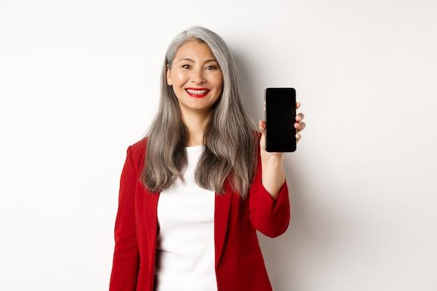 Oudere zakenvrouw in rode blazer, met leeg smartphonescherm en glimlachend, demonstreren mobiele app, witte achtergrond.